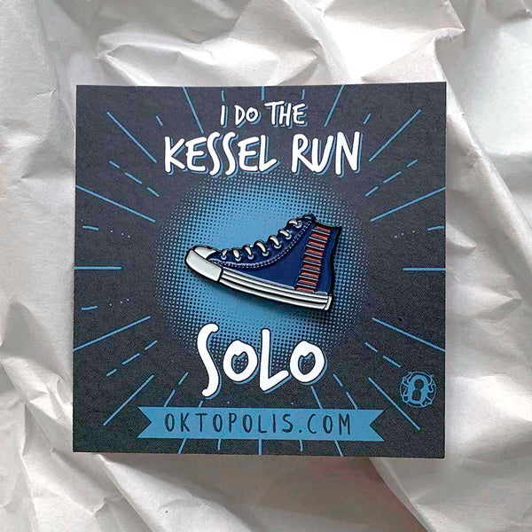 Collectable enamel pin of a tennis shoe featuring a keepsake display card with the inscription I DO THE KESSEL RUN... SOLO designed by illustrator Brian Miller for Oktopolis
