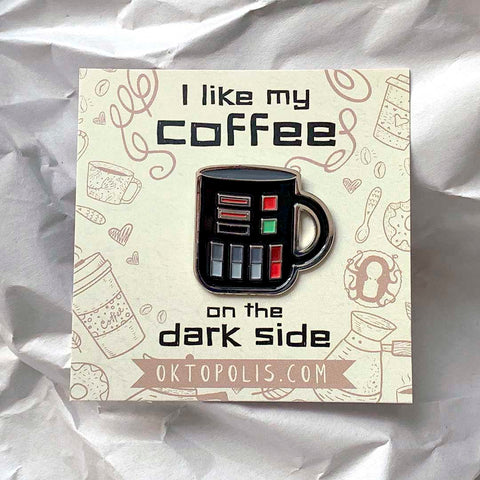 Collectable enamel pin of a black coffee mug featuring a keepsake display card with the inscription I LIKE MY COFFEE ON THE DARK SIDE designed by illustrator Brian Miller for Oktopolis