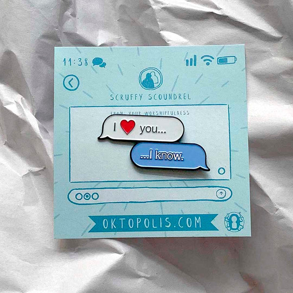 "Collectable enamel pin of chat text bubbles between two people saying I ""Heart"" You and I know featuring a keepsake display card resembling a chat display designed by illustrator Brian Miller for Oktopolis"