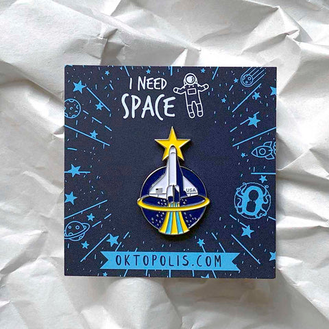 Collectable enamel pin of the Space Shuttle featuring a keepsake display card with the inscription I NEED SPACE designed by illustrator Brian Miller for Oktopolis