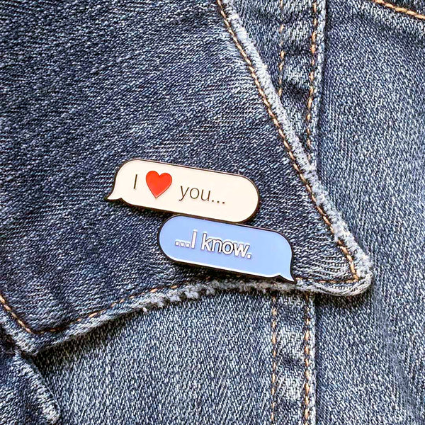"Collectable enamel pin of text message bubbles with the famous phrase ""I Love YOU,"" ""I know"" inside the text bubble. This enamel pin features a keepsake display card created to resemble a text message interface designed by illustrator Brian Miller for Oktopolis"