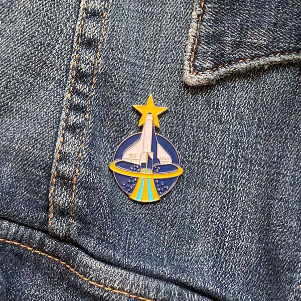 Collectable enamel pins featuring the Space Shuttle designed by illustrator Brian Miller for Oktopolis