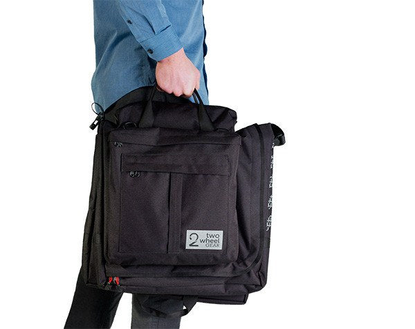 Classic 2.0 Garment Pannier being carried by briefcase handles