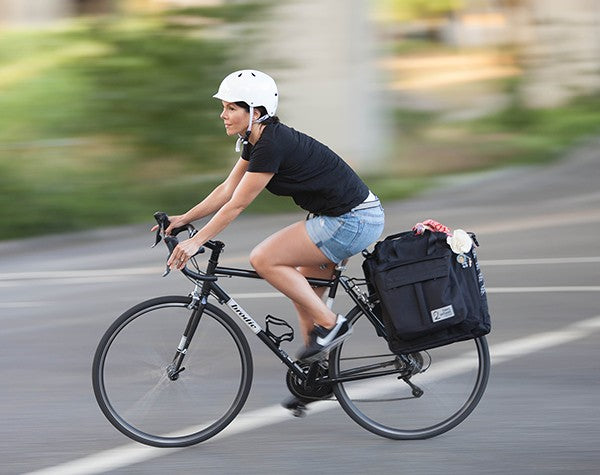 Woman riding bike with Classic 2.0 Garment Pannier in Black