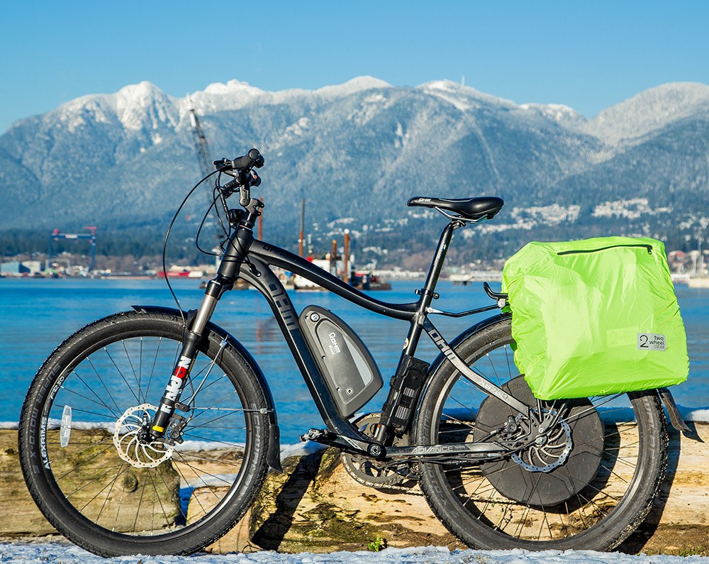 Classic Garment Pannier Replacement Rain Cover on a bike with the ocean and mountains in the backdrop