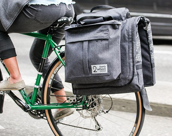 Woman riding bike with Classic 2.0 Garment Pannier in Graphite Grey
