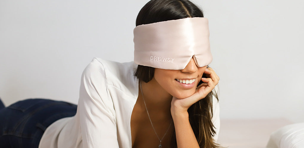Smiling model lying on her front in bed with luxury Sunset Pink Drowsy silk sleep mask over her eyes