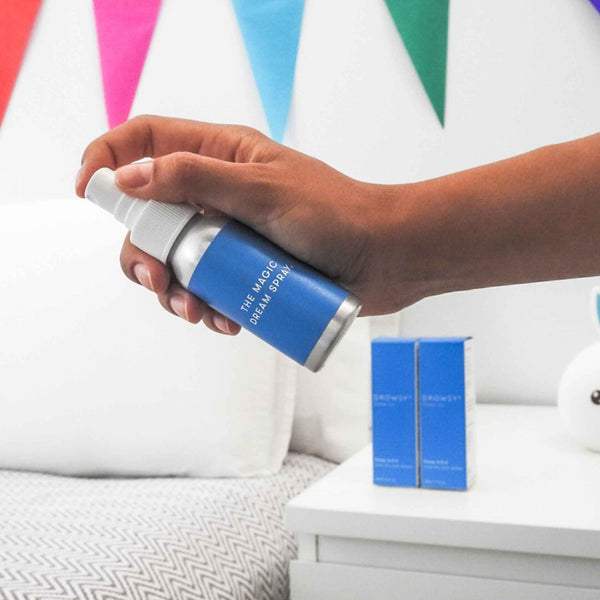 Hand spraying bottle of Drowsy Sleep SOS for kids on to pillow.