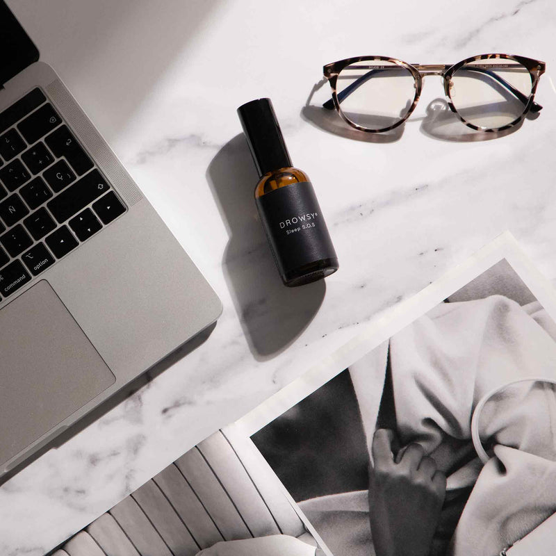 Drowsy Sleep Co. Sleep SOS Pillow spray in amber glass bottle on desk with computer, glasses and a fashion magazine.