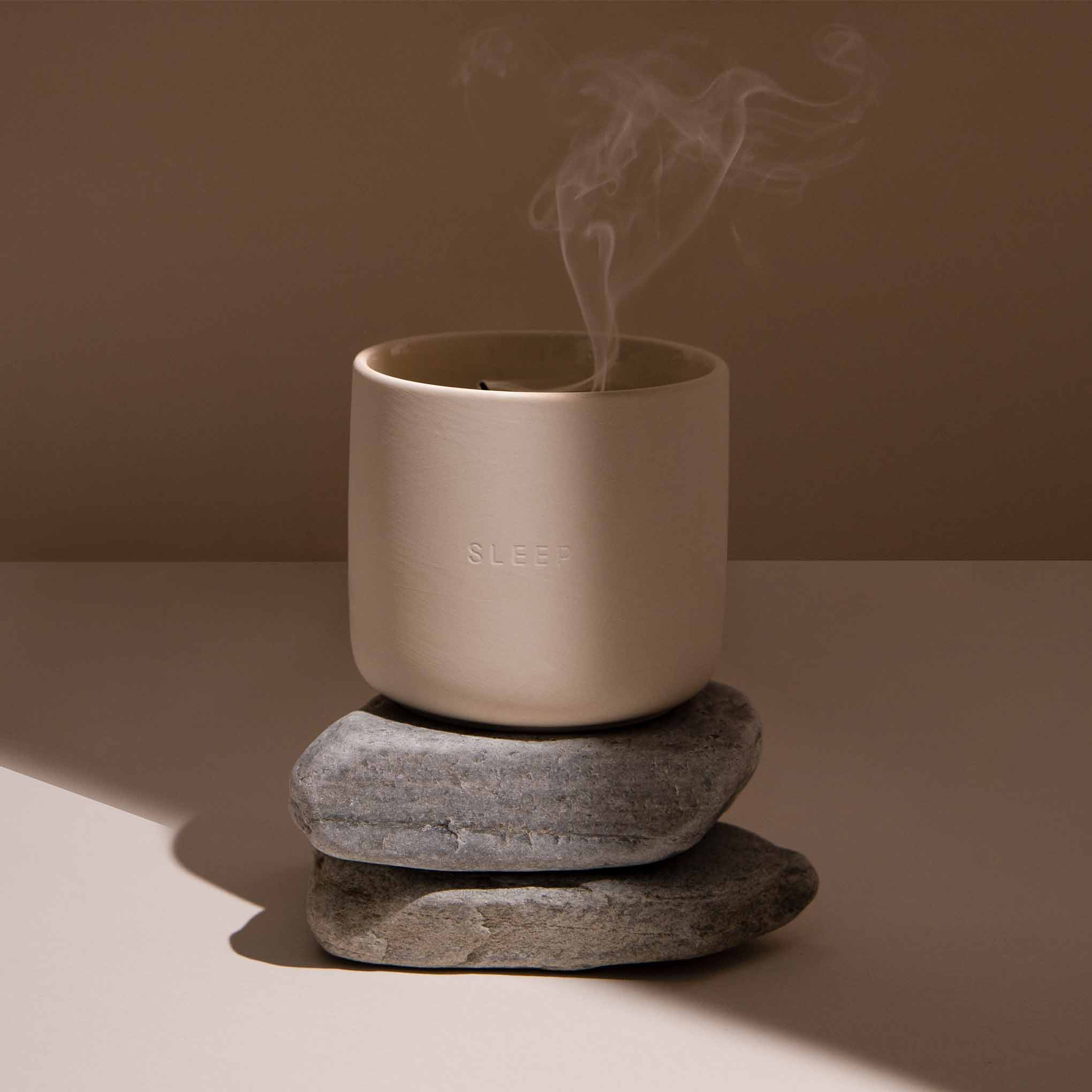Candle in ceramic jar with smoke rising from the wick