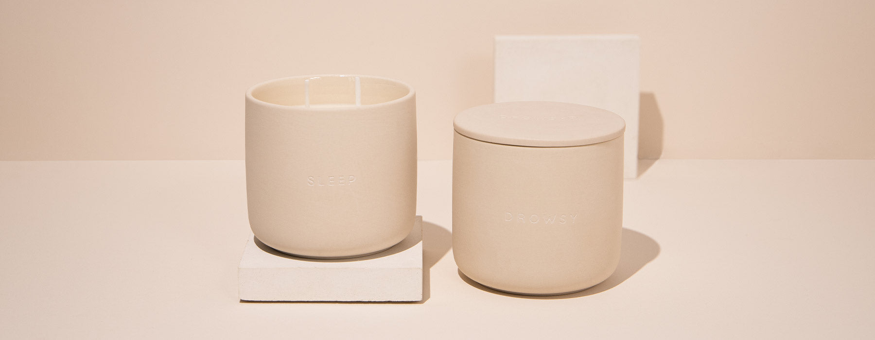 2 ceramic candle jars on a cream coloured background