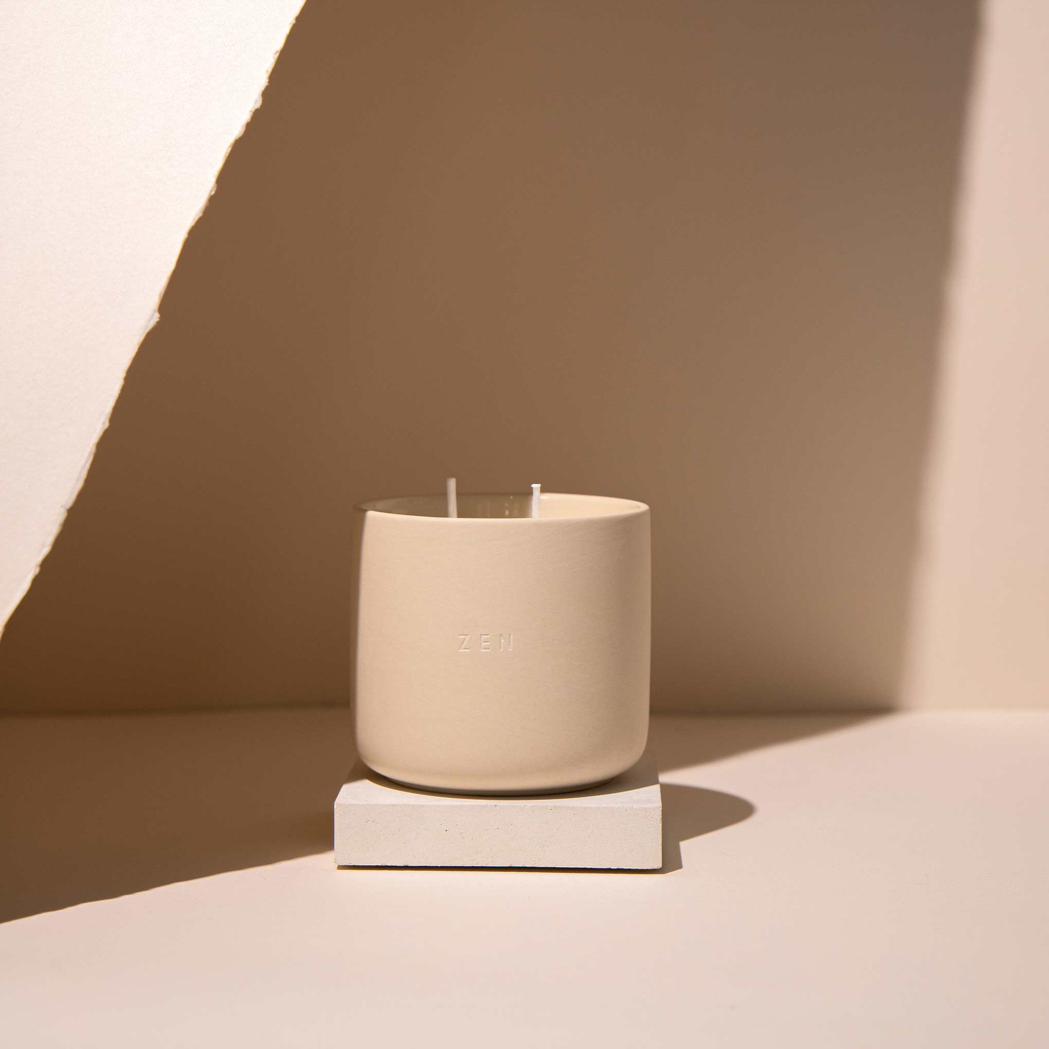 Ceramic candle jar on cream coloured background with artistic shadows