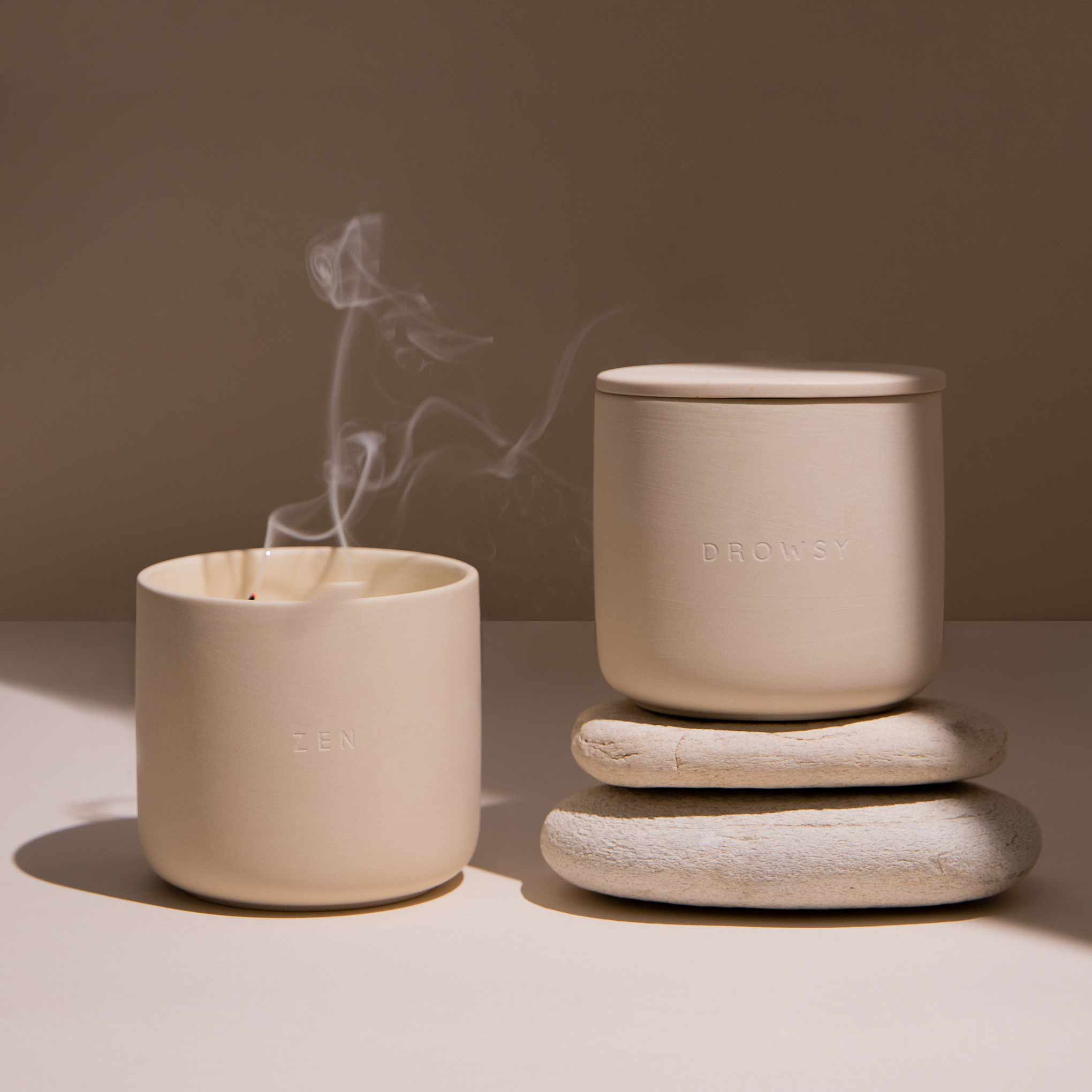 2 Candles in ceramic jars on a cream coloured background. One of them has just been blown out and has smoke gently rising from the wick.