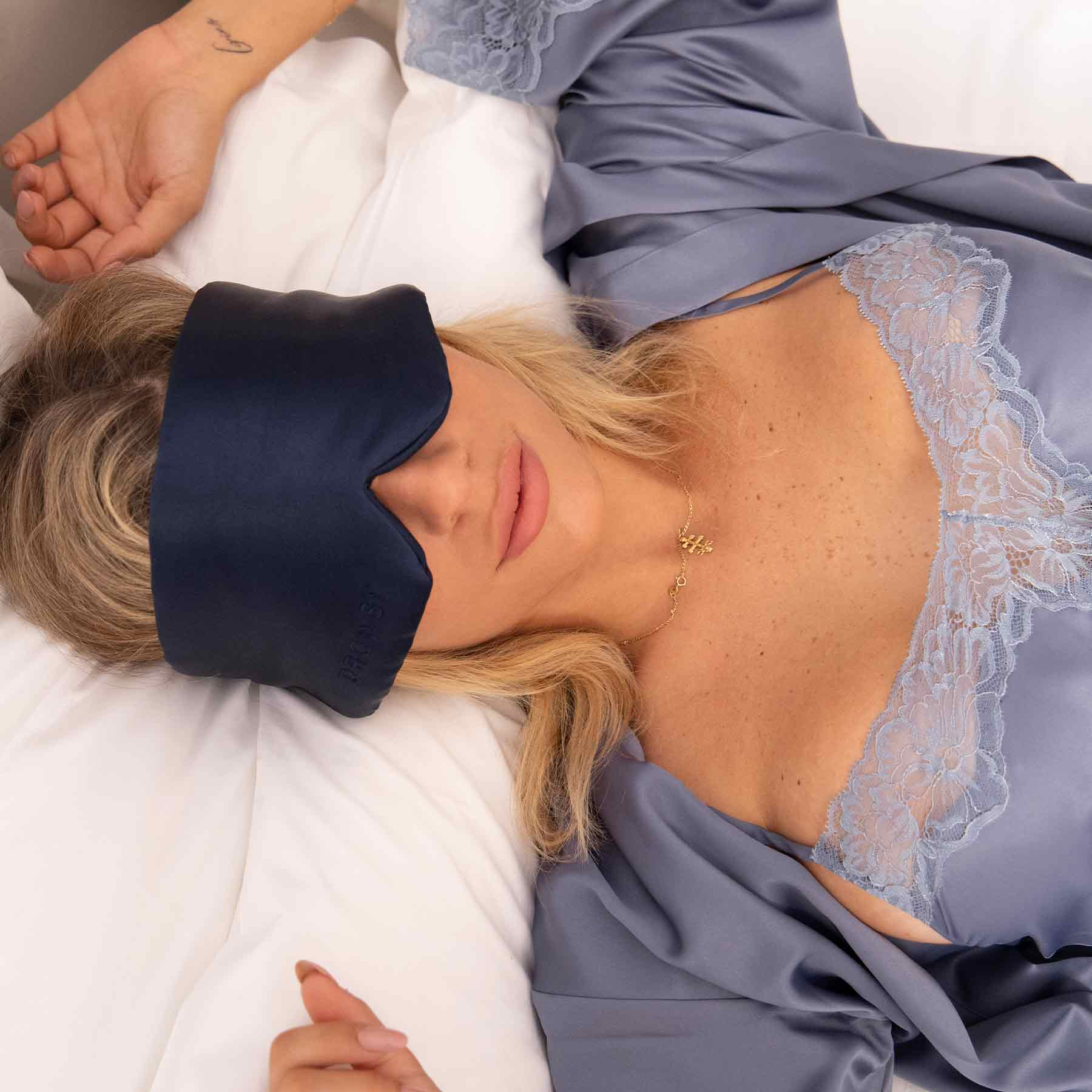 Model sleeping in bed with Drowsy Sleep Co. Midnight Blue mask covering her eyes
