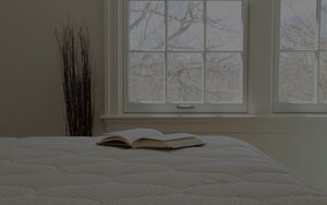 An open book on a Spindle mattress and a large window in the background showing trees with no leaves