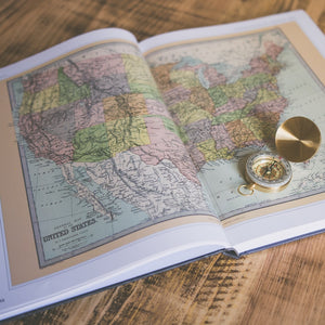 A map of the United States of America inside of a book with a gold compass resting on one page