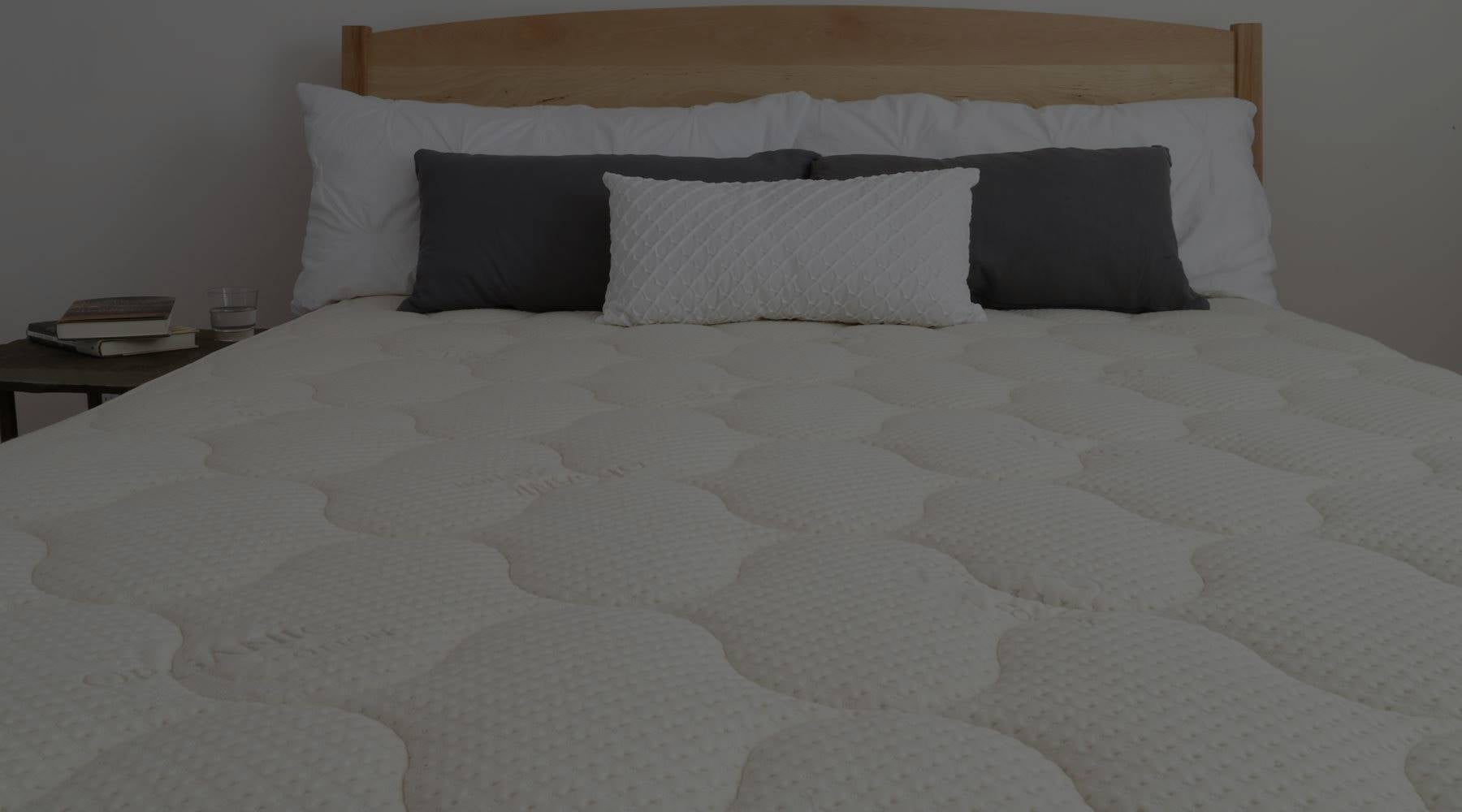 Spindle's mattress with navy blue and white pillows on wood platform bed