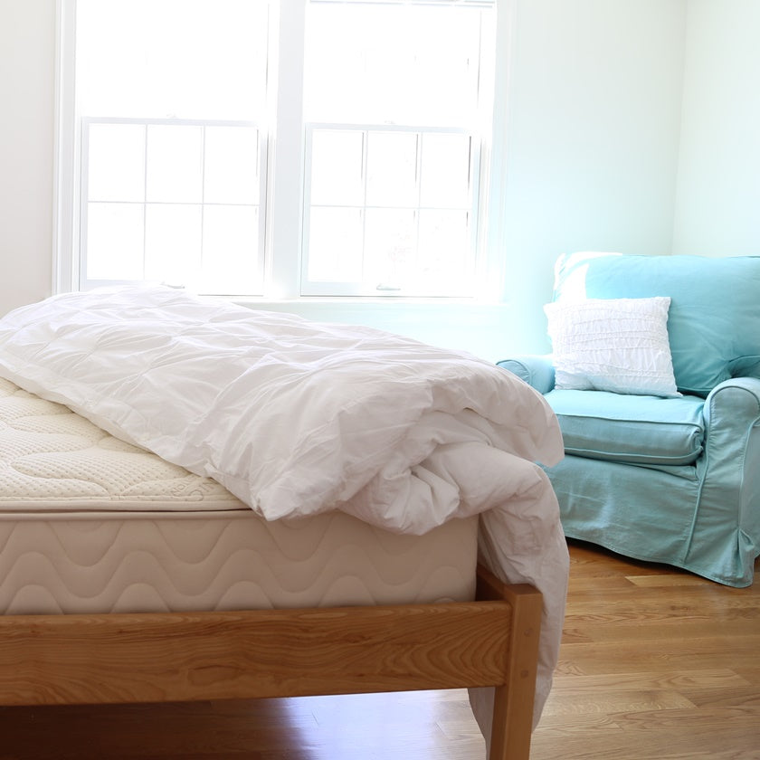 4c7382bc38878 Spindle natural latex mattress on wood platform bed and blue chair in bedroom  with sunlight coming