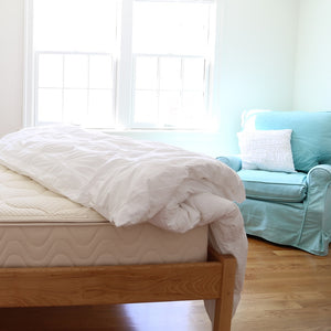 Spindle natural latex mattress on wood platform bed and blue chair in bedroom with sunlight coming through window