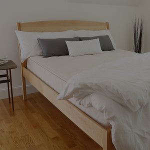 Bedroom with platform bed supporting a natural latex mattress with white comfort pulled back showing organic cotton fabric