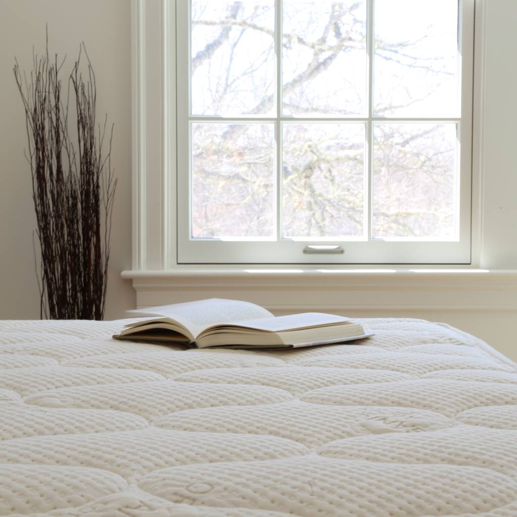 Book resting on the organic cotton fabric of a spindle mattress with large window in background