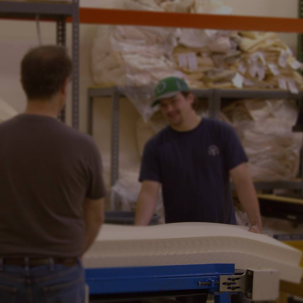 two spindle employees loading natural latex into a roll packer