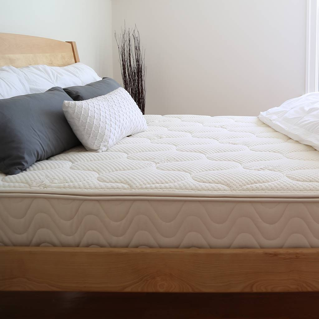 wood bed frame with latex mattress and pillows and white blanket