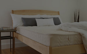 Wood bed frame supporting Spindle's Natural Latex Mattress with white and blue pillows and without sheets