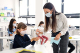 Teacher helping a student use sanitizer during covid