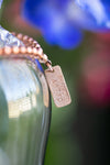 copper beaded bracelet with rose gold-filled tag hanging on a vase