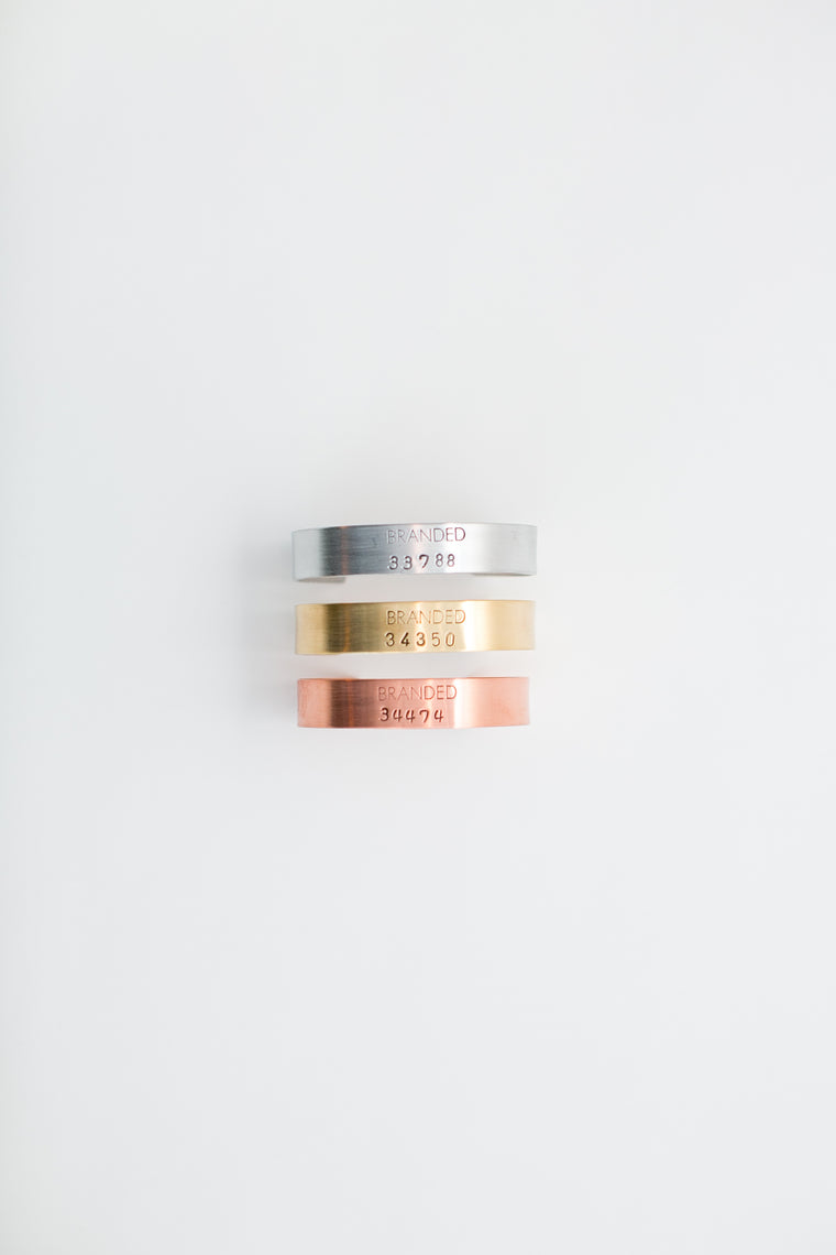 small aluminum, brass and copper cuff bracelets on a white background