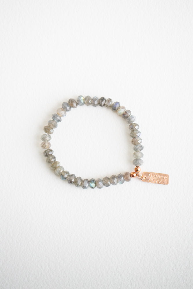 gray labradorite beaded bracelet with a rose-gold filled tag on a white background