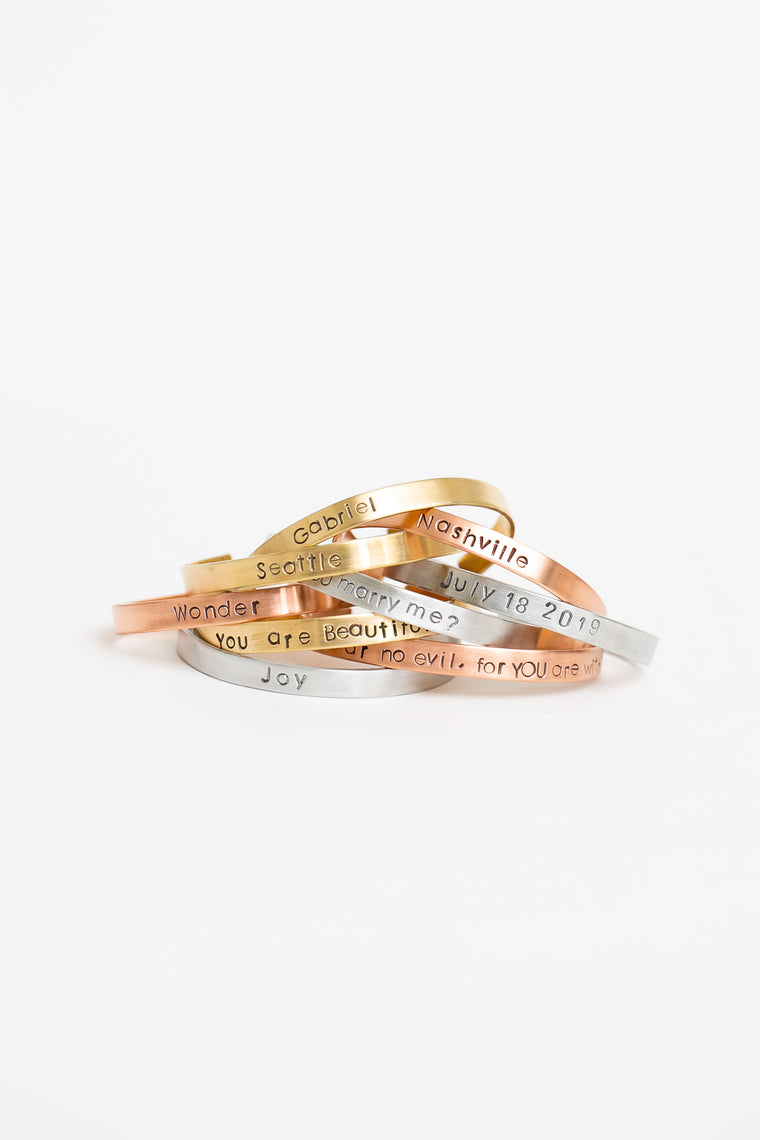 Stack of cuff bracelets with personalized stampings
