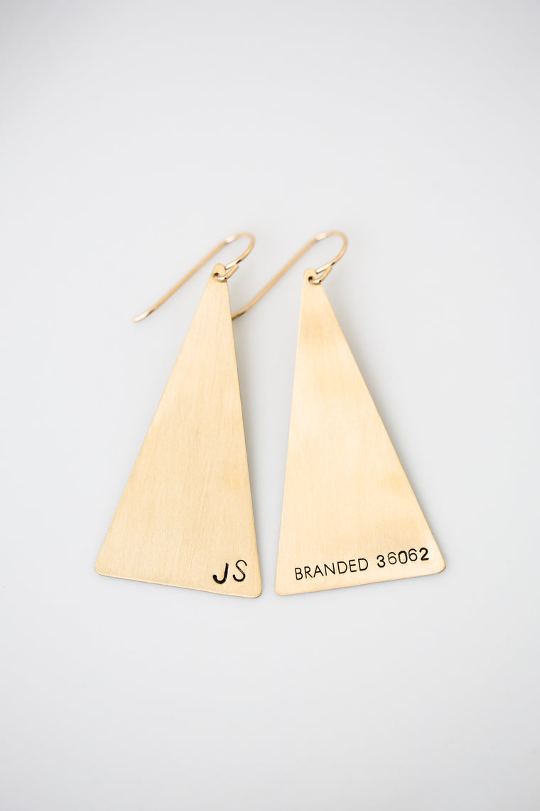 brass triangle earrings with trafficking survivor initials and BRANDED number