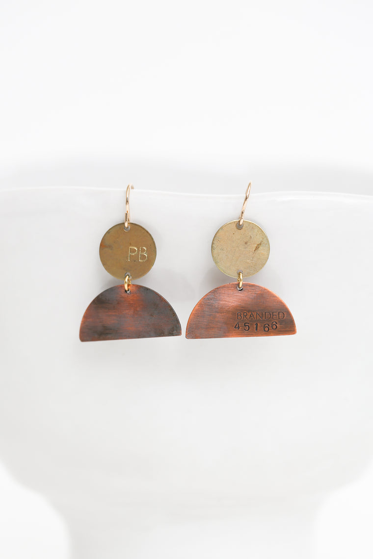 brass and copper half-moon earrings hanging on a white cup