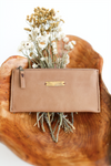 Stone leather BRANDED pouch sitting on a bunch of flowers and a wood plate