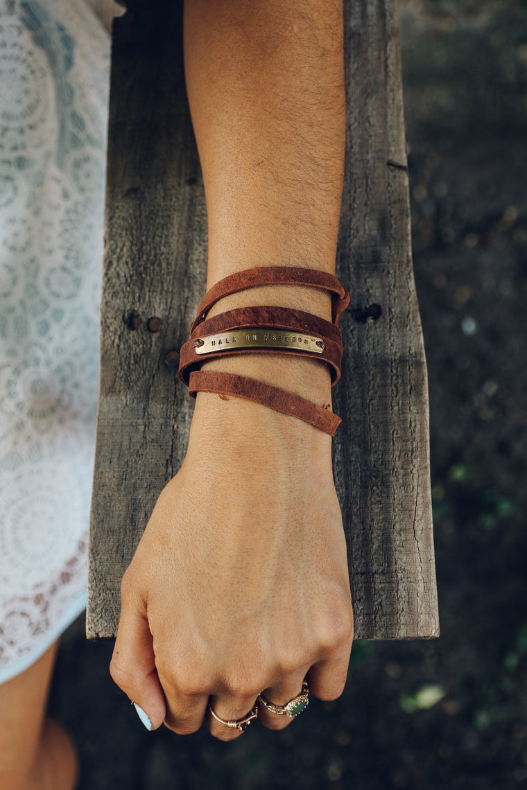 Hand wearing Walk in Freedom Leather Wrap