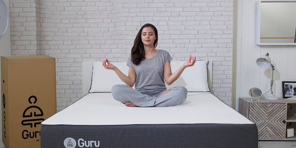 Woman meditating on the guru by zen mattress