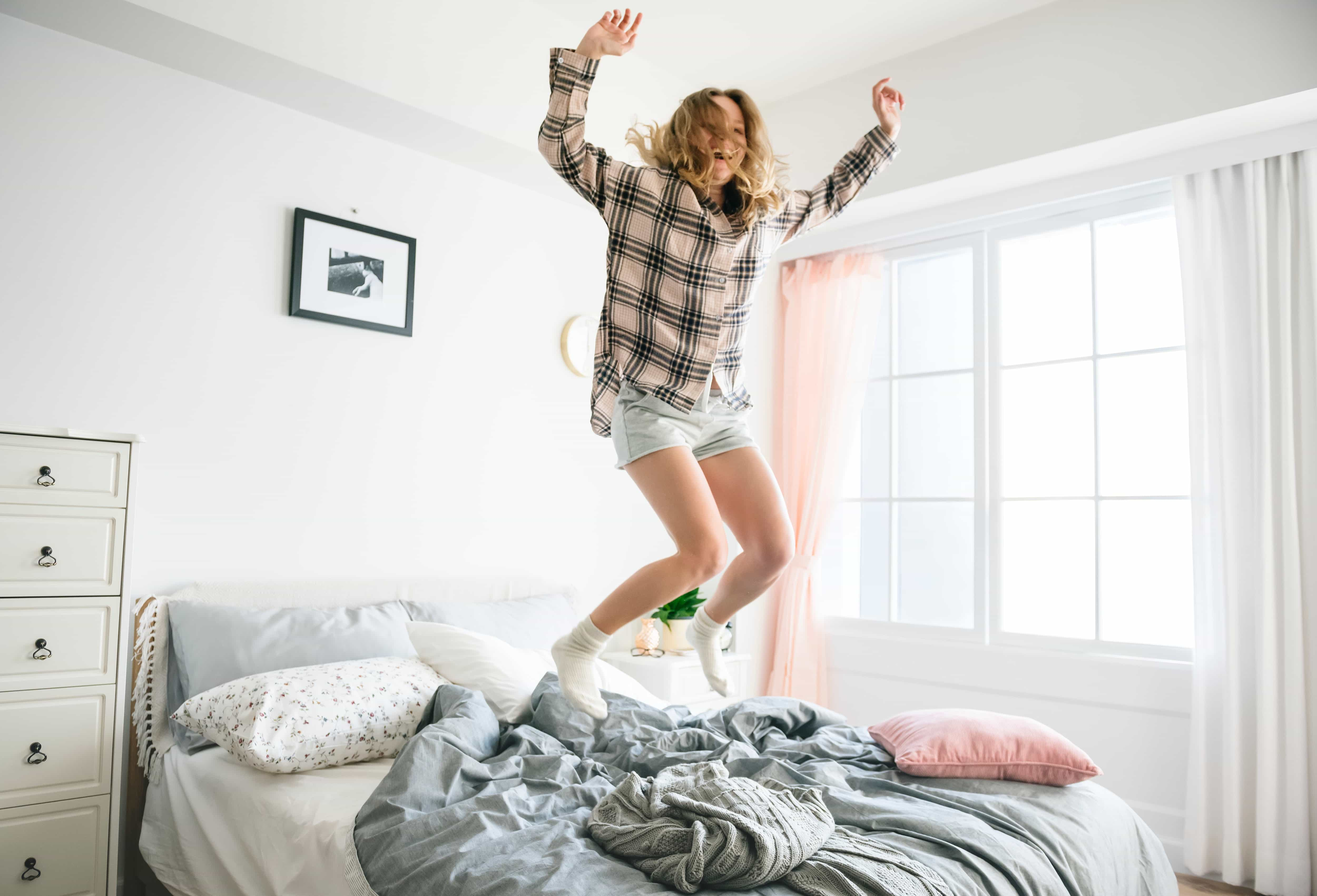 Woman jumping on a bed