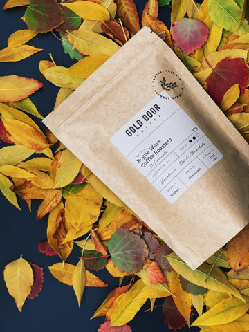 Bag of Gold Door Coffee Featured October Roaster Rogue Wave Coffee lying in a bed of leaves