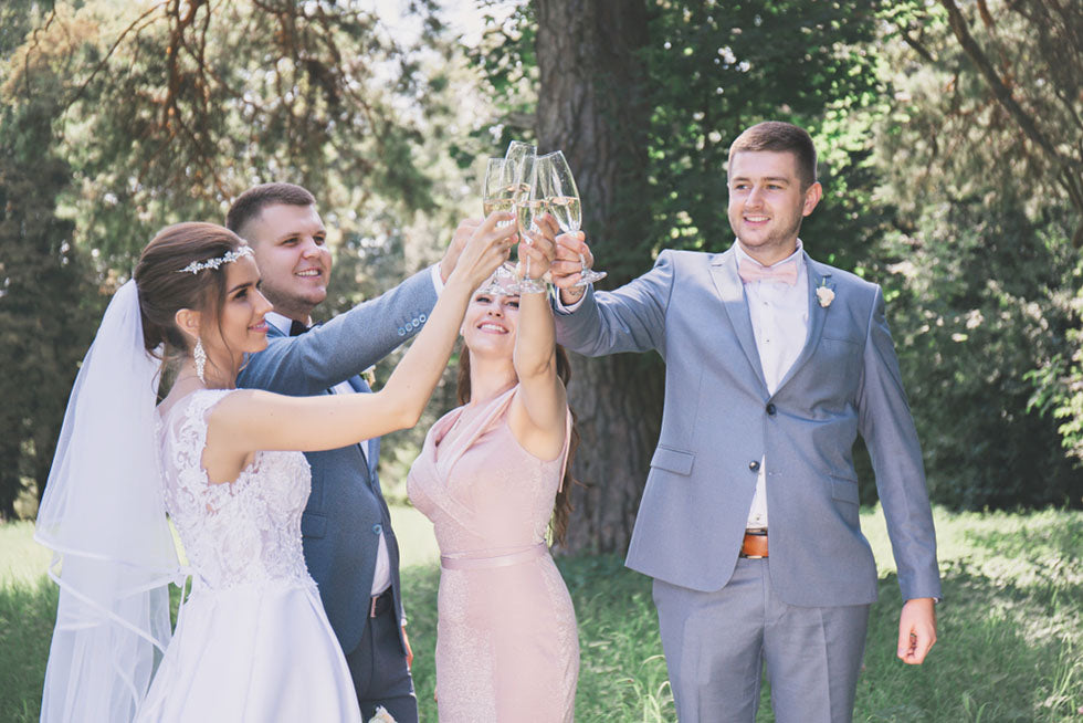 newlyweds and guests drink champagne in a park