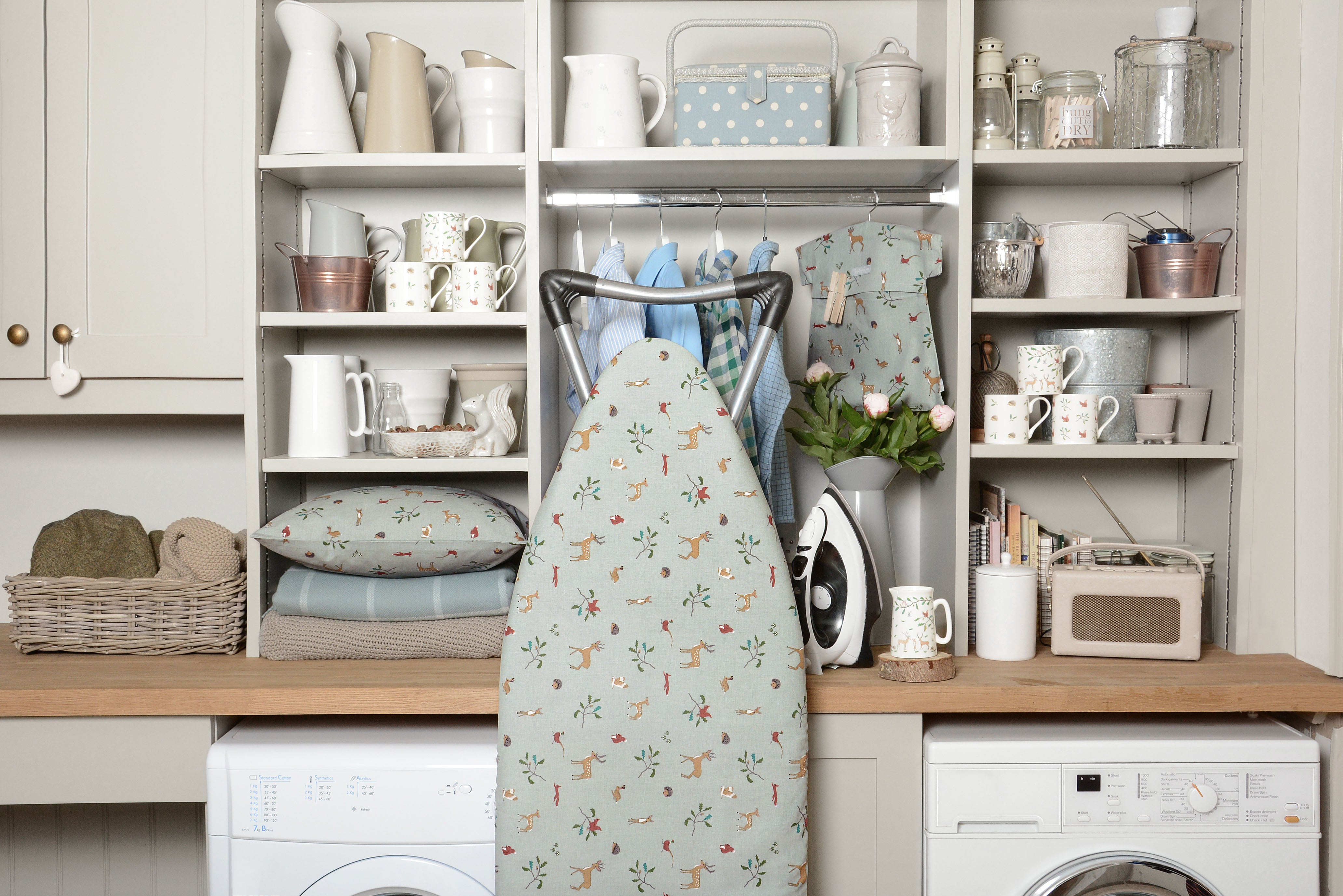 Utility room with ironing board and woodland homeware linens