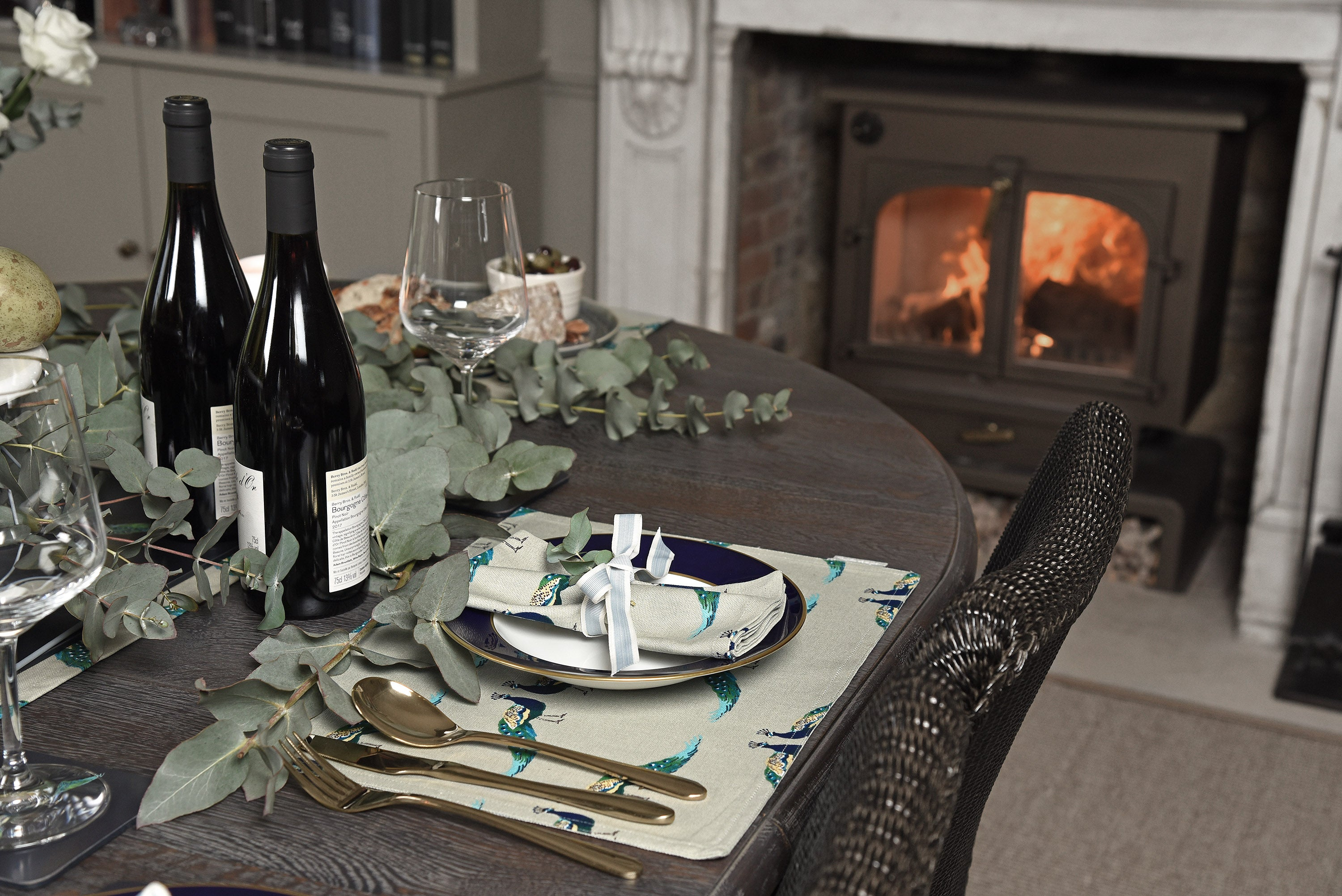 Autumn table setting ideas for your home with peacocks style placemat, napkins and cosy fire