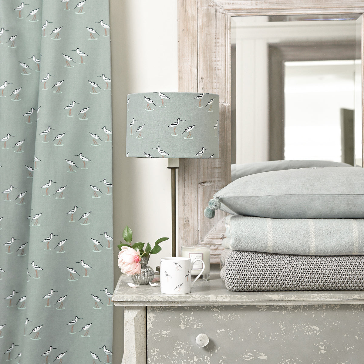 Sophie Allport's sea blue green fabric has been made into curtains and a lampshade.
