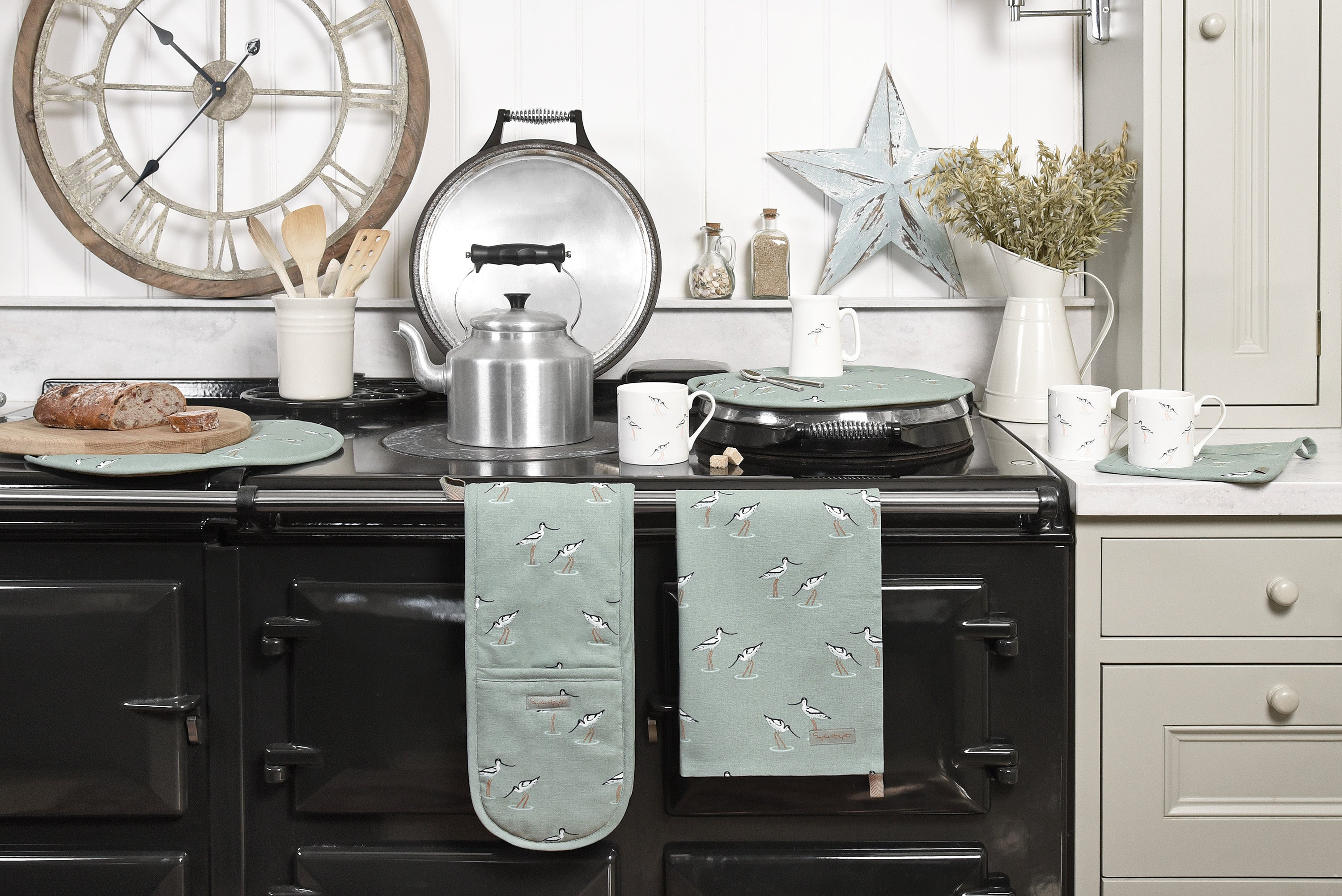 An AGA dressed in Sophie Allport's sea blue green coastal birds collection featuring elegant avocets, including tea towel, oven globes, hob cover, mugs and jugs.