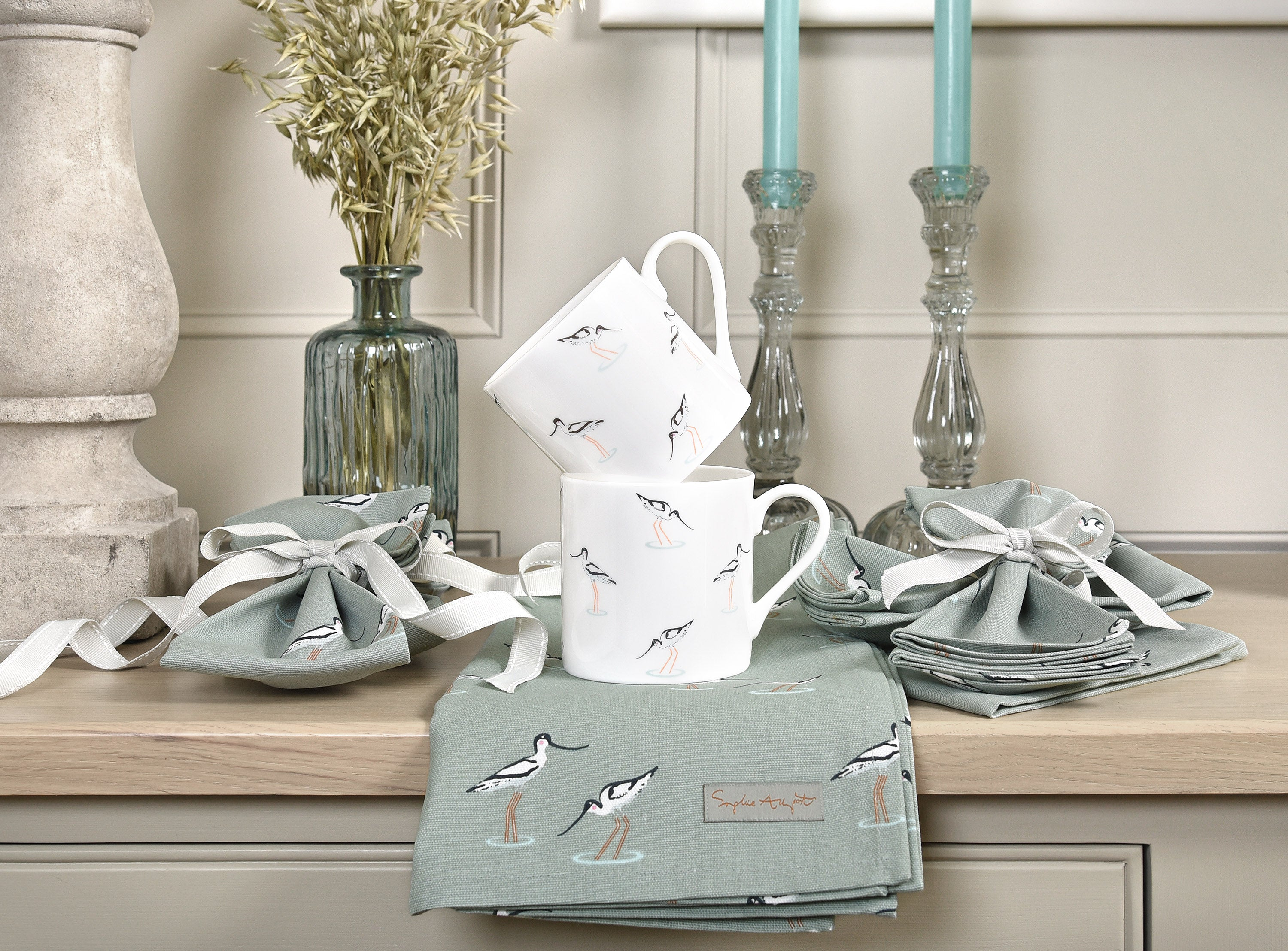 Sophie Allport's avocets mugs stacked up on a beautiful dresser
