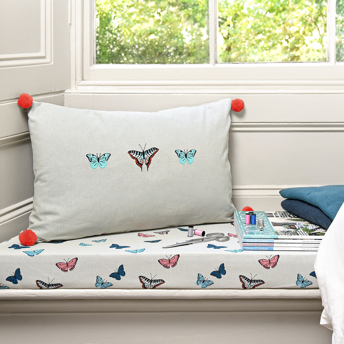 Butterflies Cushion by Sophie Allport with pink pom pom detailing.