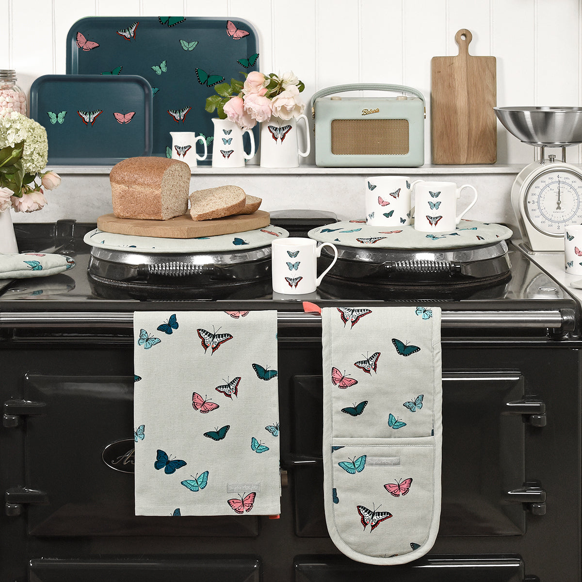 Colourful butterflies sit on this Sophie Allport tea towel with a soft neutral background.