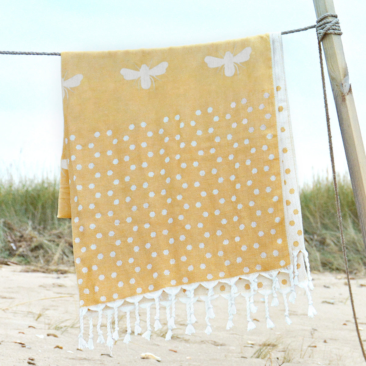 Sophie Allport's yellow hammam towel covered white bees, perfect for the park or beach.