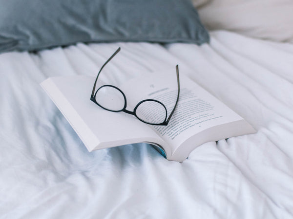 Artistic image of eyeglasses and a book alone on a bed
